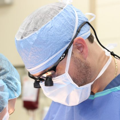 A veterinarian currently performing surgery. Vet is dressed in scrubs and wearing a mask, cap and glasses